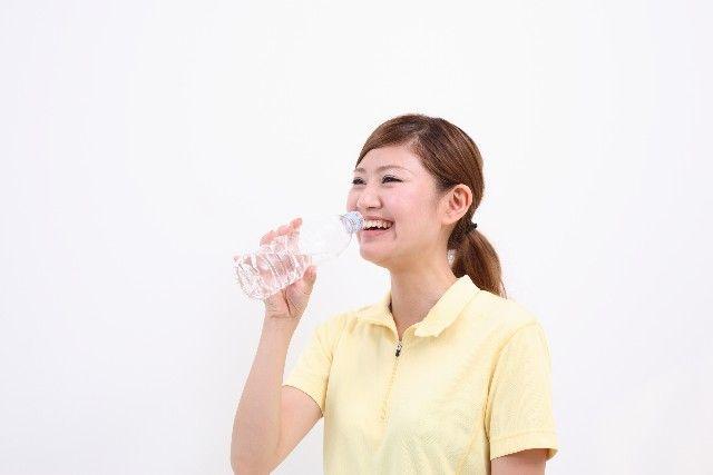 ペットボトルで水を飲む女性