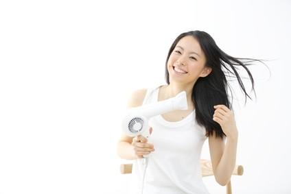 笑顔で髪をドライヤーで乾かす女性