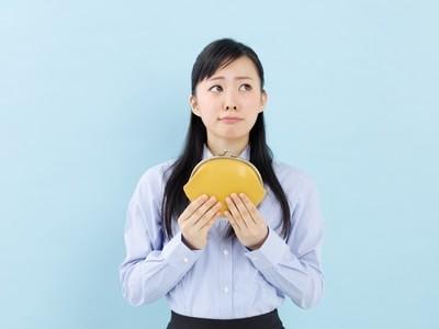 黄色い財布を持ち考える女性