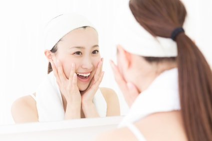 鏡をみて肌の状態に喜ぶ女性