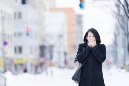 冬の外で手に息を吹きかける女性