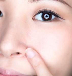 小鼻を指さす女性