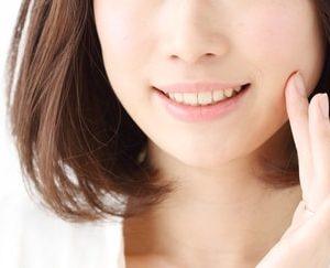 頬を指で触る女性
