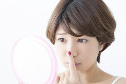 鏡を見て鼻のニキビを気にする女性