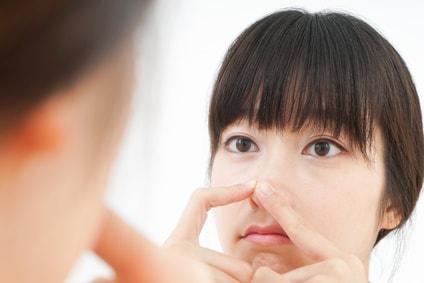 鏡を見ながら鼻を気にする女性